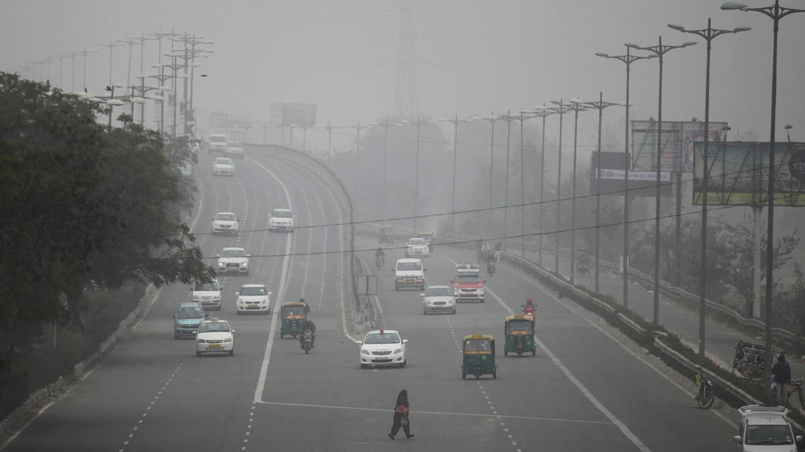 In this Jan. 15, 2016, file photo, an Indian woman crosses a road as vehicles move through morning smog on the last day of a two-week experiment where the Delhi government allowed private cars on the roads on alternate days depending on whether their license plates end in an even or an odd number, to reduce the number of cars to fight pollution in New Delhi, India. (AP)