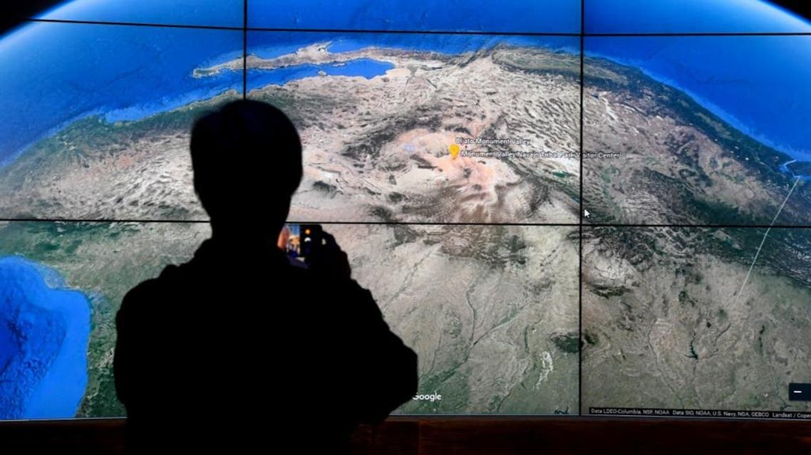 A man looks at a Google Earth map on a screen as Google Earth unveils the revamped version of the application. (AFP)