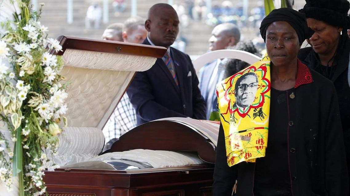 A mourner with a regalia bearing the face of Mugabe, walks after paying her last respects to Robert Mugabe's body as it lies in state at the at Rufaro stadium. (Reuters)