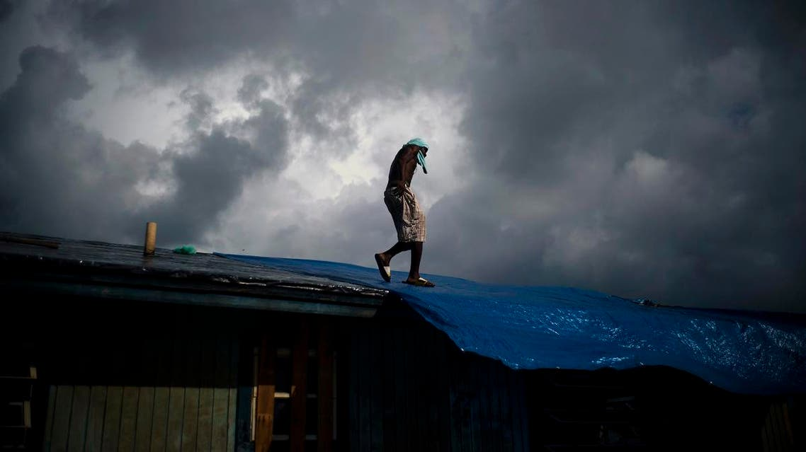 Trevon Laing walks the roof of his house to repair the damage made by Hurricane Dorian, in Gold Rock Creek, Grand Bahama, Bahamas. (AP)
