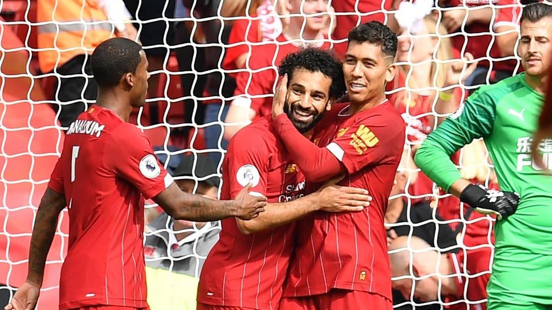 Liverpool's Egyptian midfielder Mohamed Salah (CL) celebrates with Liverpool's Brazilian midfielder Roberto Firmino (R) after scoring the team's third goal. (AFP)