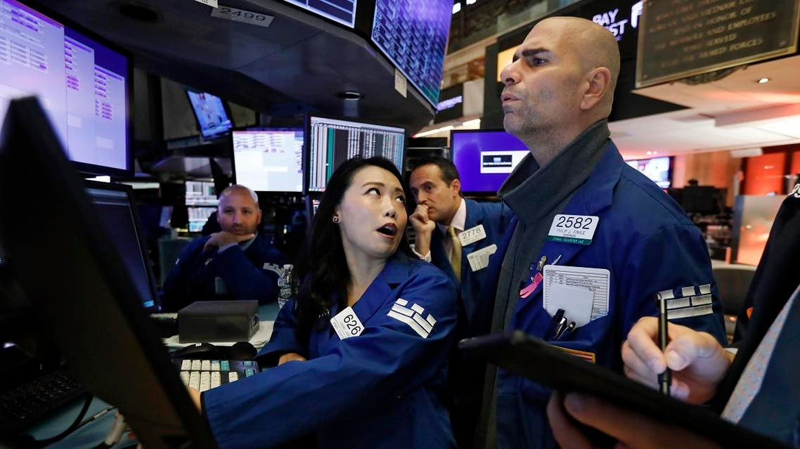 Specialist Lingbo Jiang, and Philip Finale confer as they work on the floor of the New York Stock Exchange. (AP)