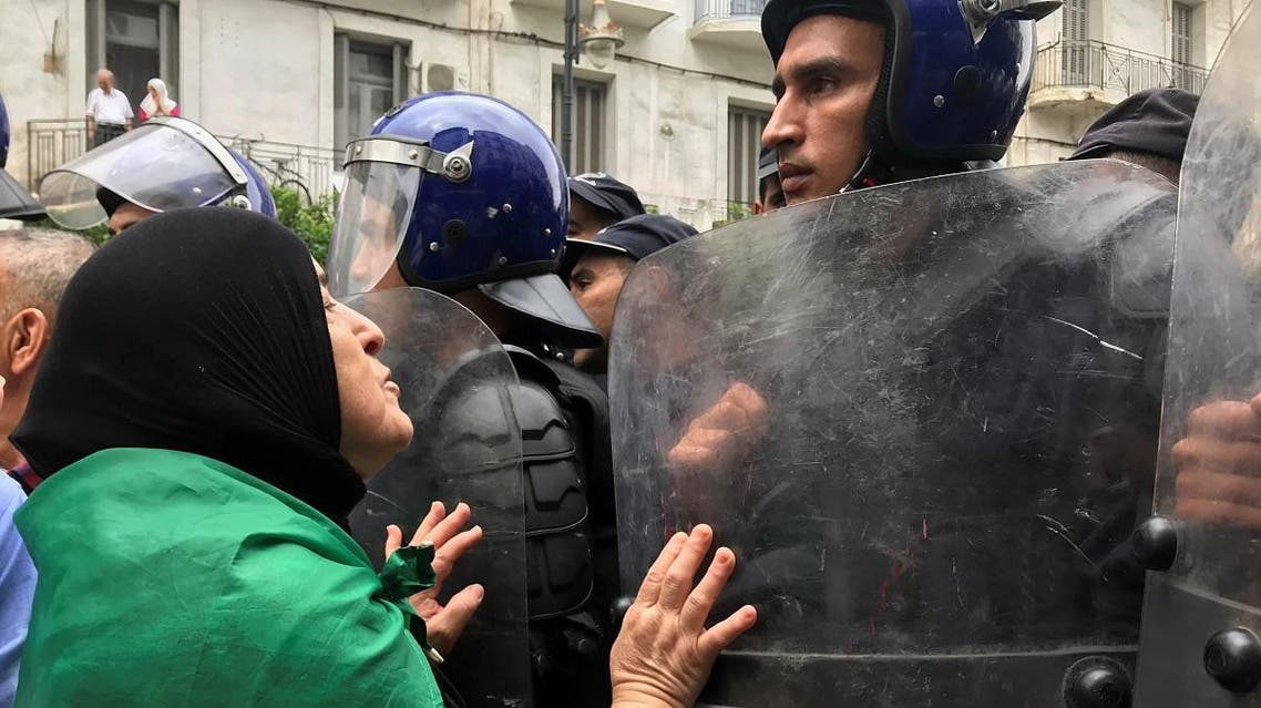 A demonstrator approaches police officers during a protest in Algiers. (Reuters)