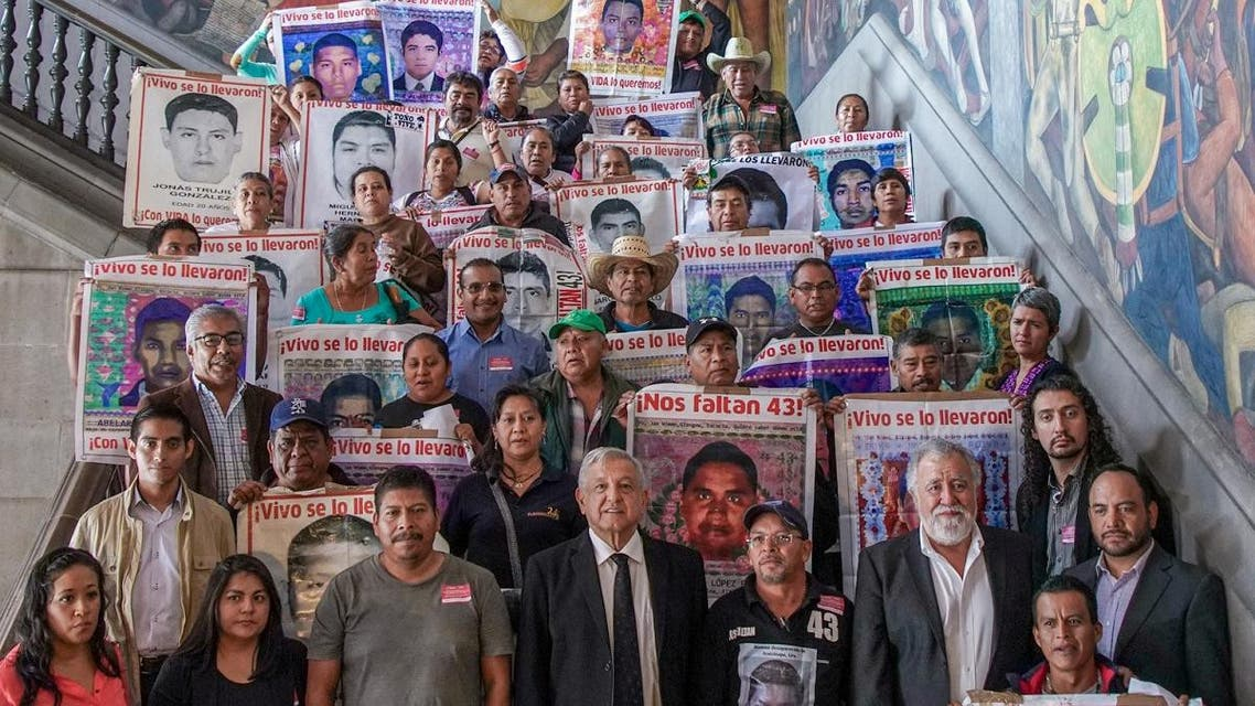 Mexico's President Obrador, Undersecretary of Human Rights Rodriguez and relatives holding posters with images of missing Ayotzinapa Raul Isidro Burgos Rural Teachers' College students pose after a meeting in Mexico City. (Reuters)