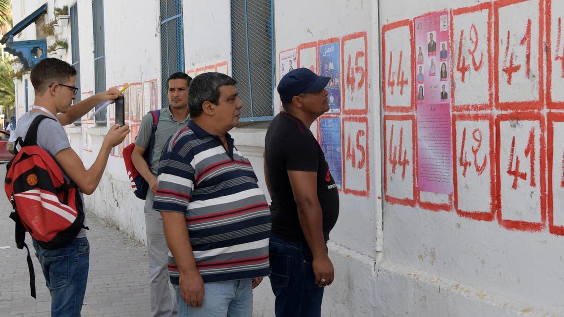ناخبون تونسيون ينظرون إلى قوائم المرشحين للانتخابات الرئاسية (في 14 سبتنبر - فرانس برس)