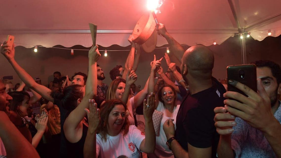 Supporters of Tunisia's jailed presidential candidate Nabil Karoui (not pictued) celebrate in front of his headquarters in the Tunisian capital Tunis on September 15, 2019. (AFP)