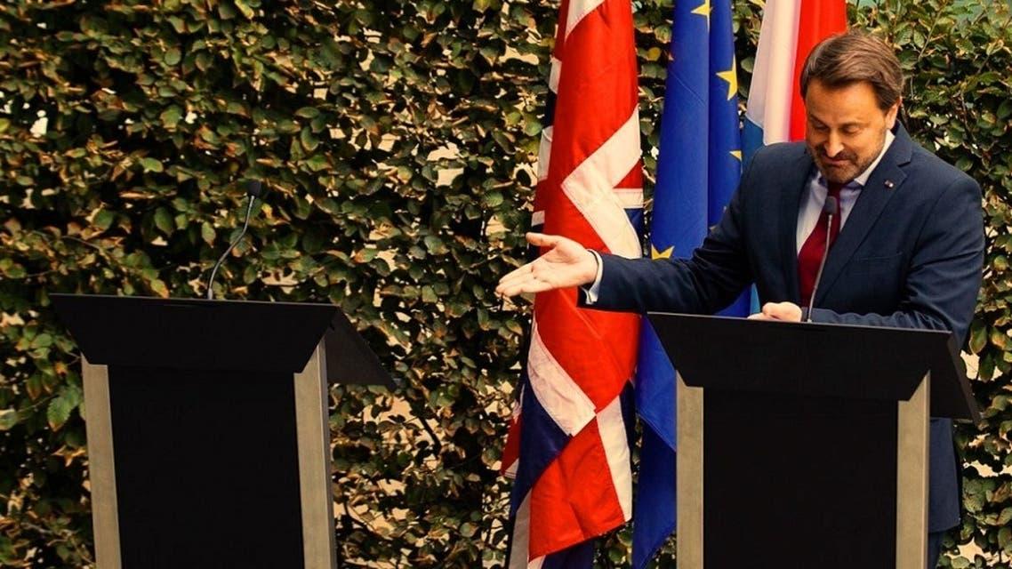 رئيس وزراء لوكسمبورغ، يشير الى جونسون كأنه حاضر، وهو غائب