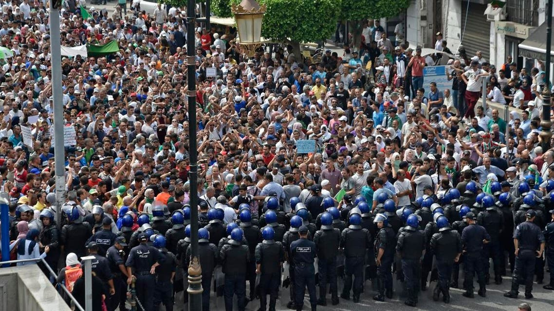Algerian security forces form a human barrier in front of demonstrators taking part in a rally in the streets of the capital Algiers on September 17, 2019. (AFP)