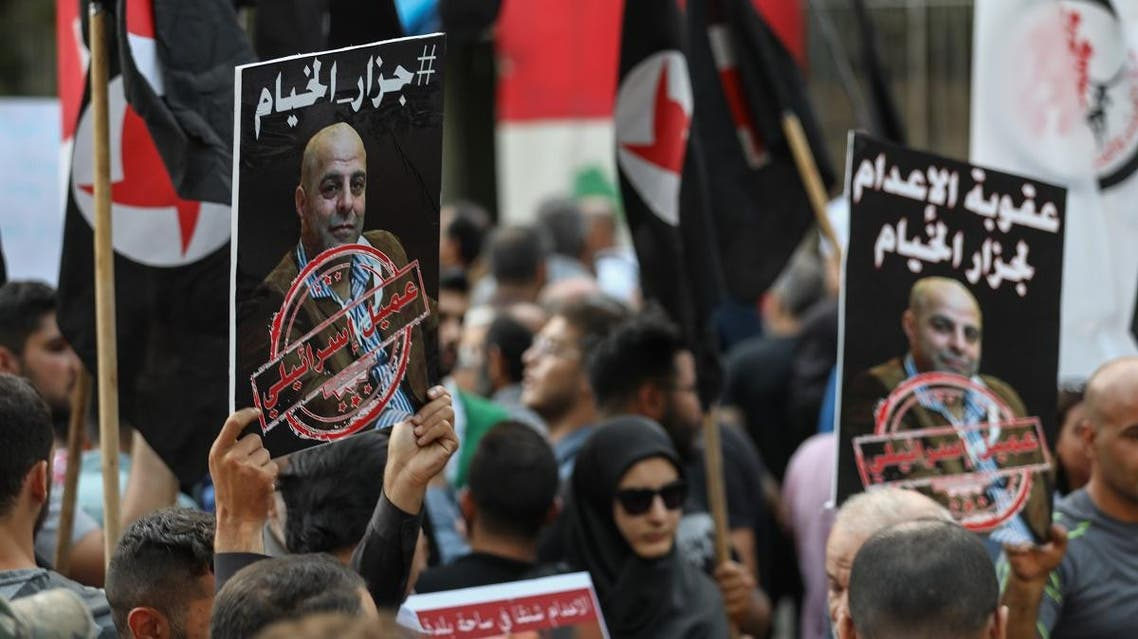 Former detainees of the pro-Israel South Lebanon Army (SLA) militia hold posters depicting former SLA member Amer al-Fakhoury during a demonstration denouncing his return and entry outside the Justice Palace in the Lebanese capital Beirut on September 12, 2019.(AFP)