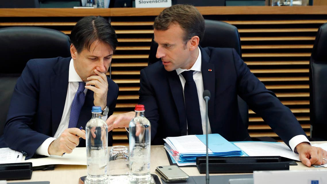 Italian Prime Minister Giuseppe Conte (L) speaks with French President Emmanuel Macron during an informal EU summit on migration at the EU commission in Brussels on June 24, 2018. EU leaders headed to Brussels for emergency talks over migration as Italy's new populist cabinet turned away another rescue ship, vowing no longer to shoulder Europe's migrant burden.