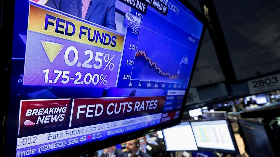 A screen displays the U.S. Federal Reserve interest rates announcement as traders work on the floor of the NYSE in New York. (Reuters)