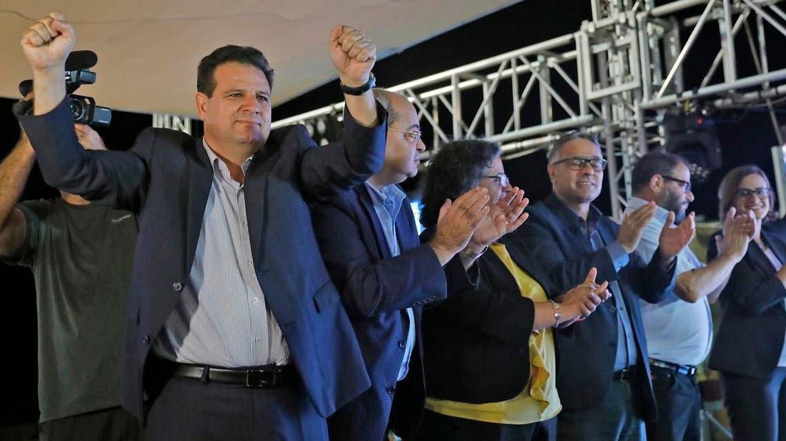 (L to R) Ayman Odeh, Israeli Arab politician and head of the Hadash (Democratic Front for Peace and Equality) party which is part of the Joint List electoral alliance, Arab Movement for Change (Taal) party's leader and candidate Ahmad Tibi, Hadash member and candidate Aida Touma, Balad (National Democratic Alliance) party member and candidate Mtanes Shehadeh, Hadash's Jewish member and candidate Ofer Cassif, and Balad member and candidate Heba Yazbak stand before supporters at the Joint List's campaign headquarters in the northern Israeli city of Nazareth on September 17, 2019, as the first exit polls are announced on television. (AFP)