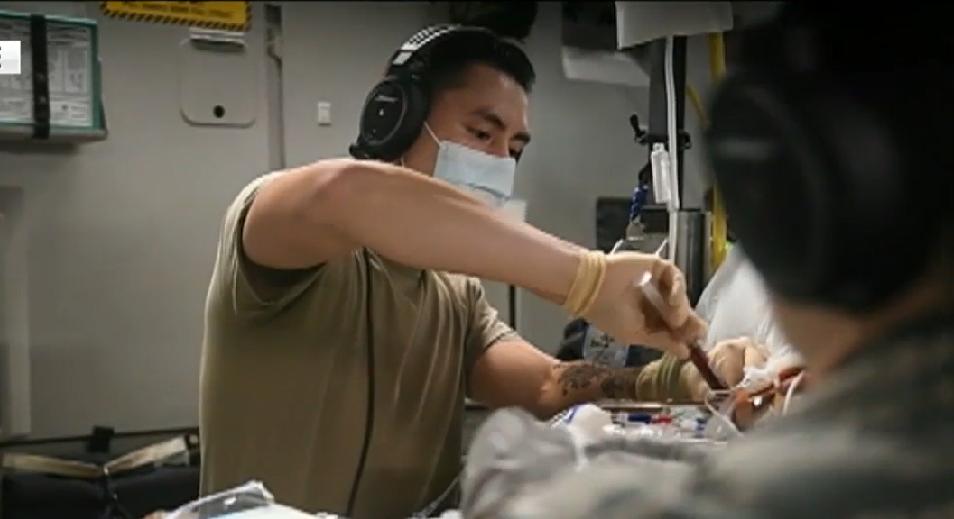 کادر پزشکی هواپیما در حال معالجه سرباز