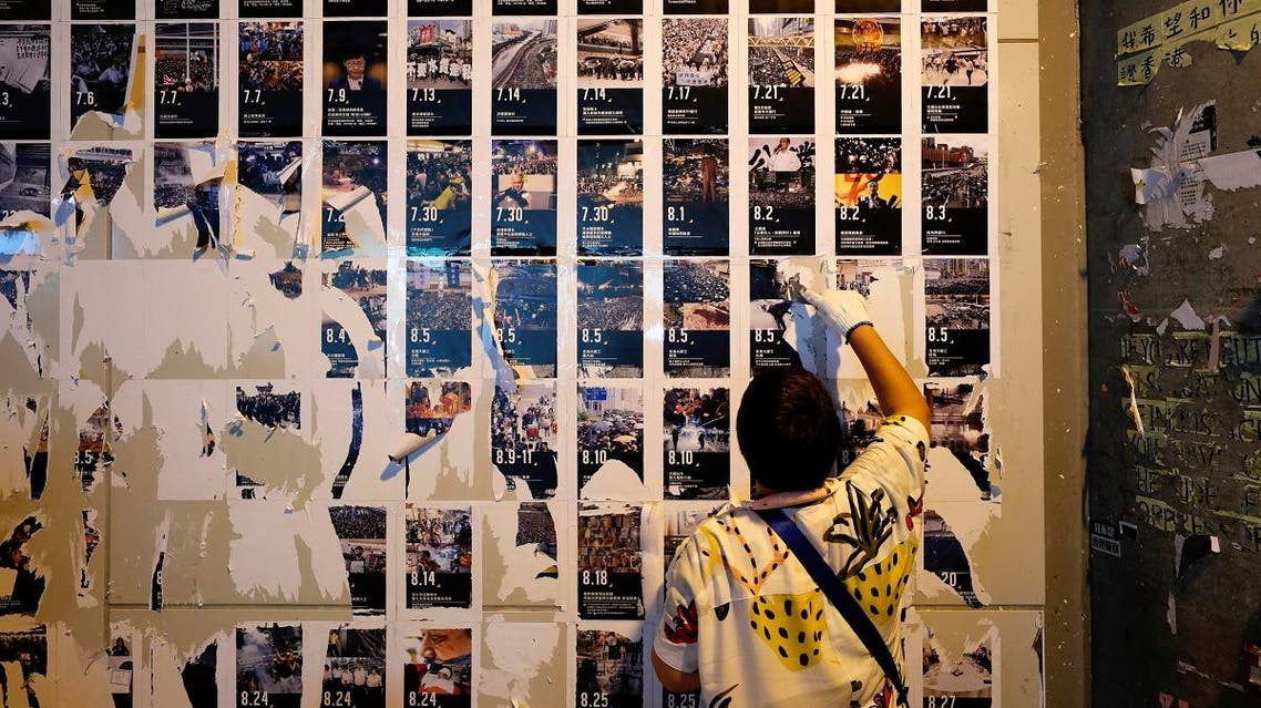 By mid-morning, dozens of Beijing supporters had started to tear down the large mosaics of colorful posted notes calling for democracy in Hong Kong. (Reuters)