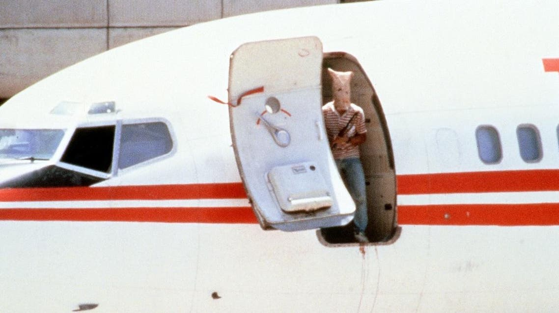 One of two heavily-armed Lebanese Shiite militants, his face hidden with a bag, who hijacked a TWA passenger Boeing 727 aircraft, looks out from the door of the jetliner on June 20, 1985 at Beirut airport. (File photo: AFP)