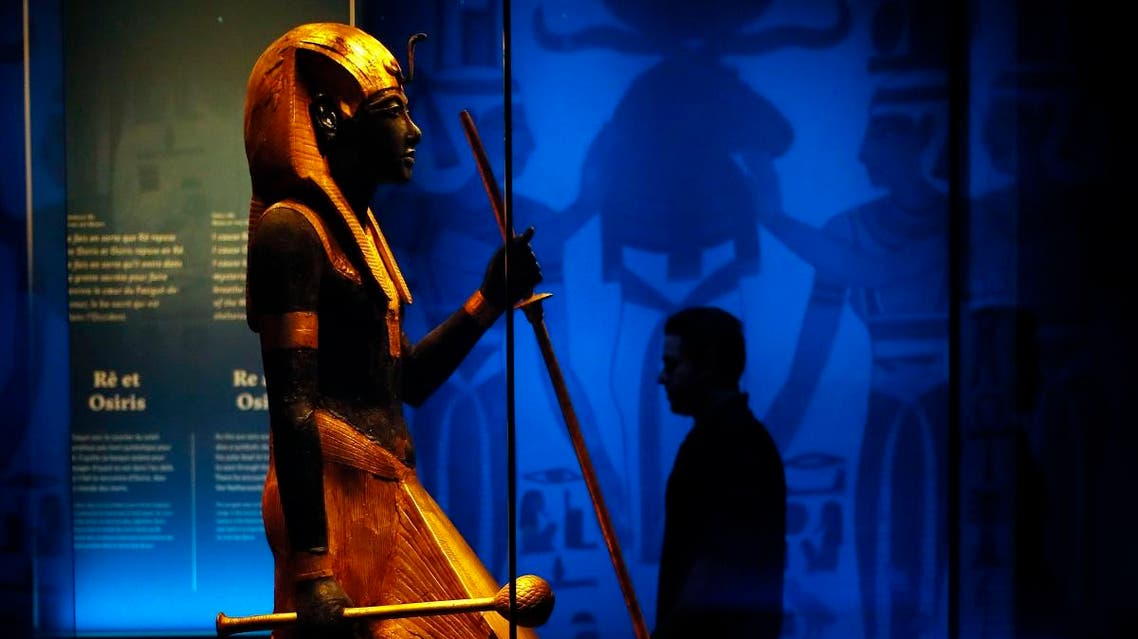 A visitor walks by a wooden guardian statue of the Ka of the king wearing the Names Headcloth displayed as part of 'Tutankhamun, the treasure of the Pharaoh', an exhibition in partnership with the Grand Egyptian Museum at the Grande Halle of La Villette in Paris. (AP)
