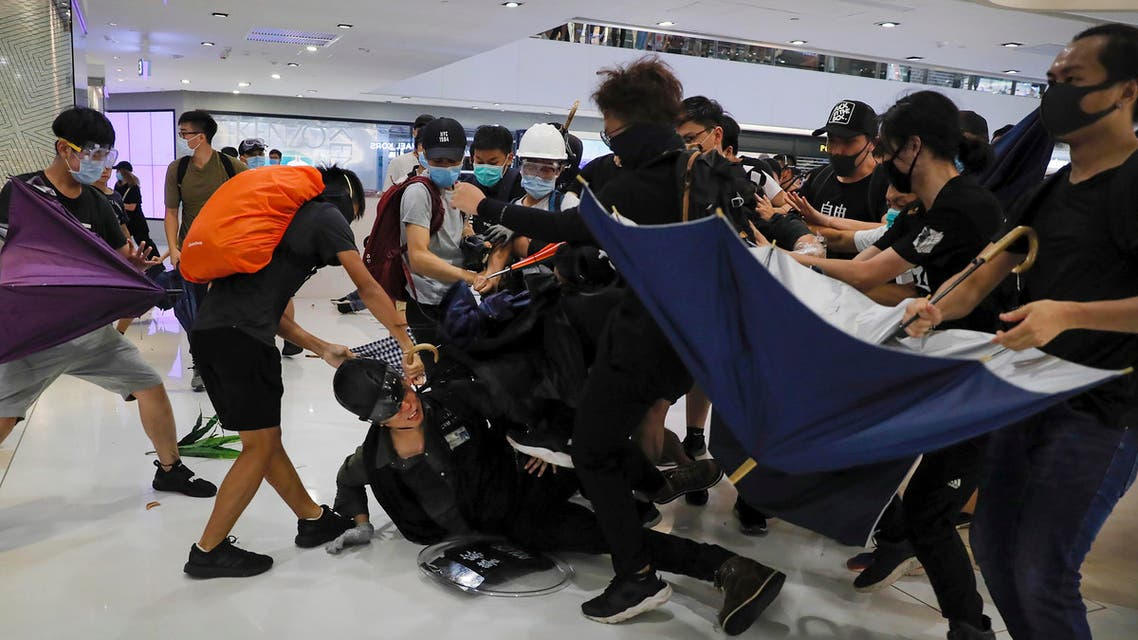 A policeman is attacked by protesters inside a mall in Sha Tin District in Hong Kong, Sunday, July 14, 2019. (AP)