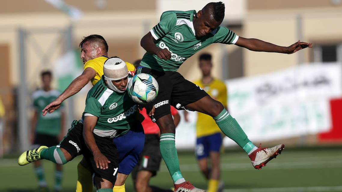 Players of Khadamat Rafah Club vie for the ball against Balata Sports Centre during the first leg match of the Palestine Cup final in Rafah in the southern Gaza Strip on June 30, 2019.