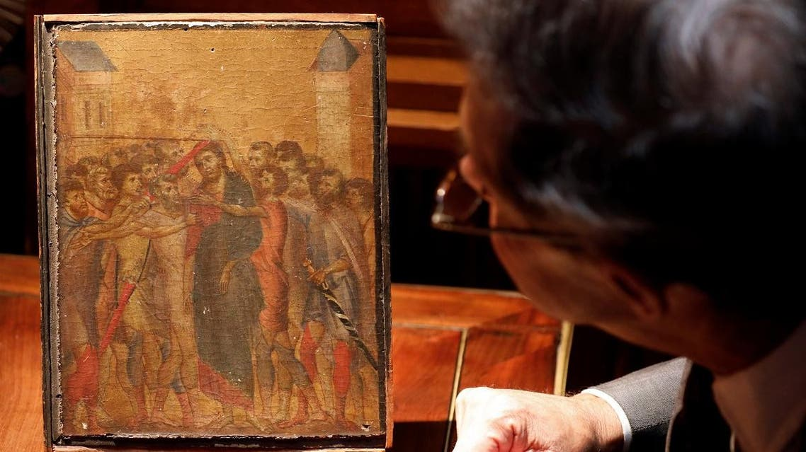 """Art expert Eric Turquin inspects the painting """"Christ Mocked"""", a long-lost masterpiece by Florentine Renaissance artist Cimabue in the late 13th century, which was found months ago hanging in an elderly woman's kitchen in the town of Compiegne, displayed in Paris, France, September 24, 2019. REUTERS"""