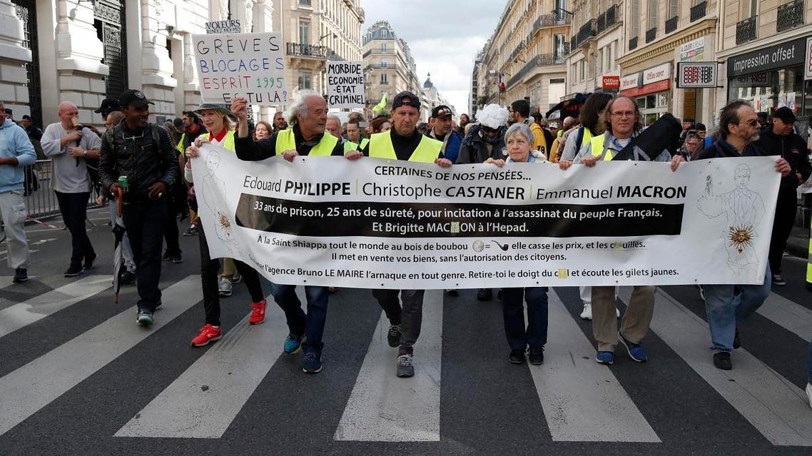 """Protestors hold a banner againt the French government as take part in an anti-government """"yellow vests"""" (gilets jaunes) protest on Place de la Bourse, Paris on September 28, 2019. (AFP)"""