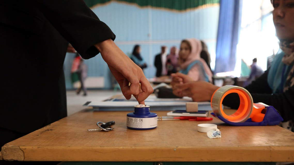 An Afghan woman, left, inks her finger at a polling station at Amani high school, near the presidential palace in Kabul, Afghanistan, Saturday, Sept. 28, 2019. (AP)