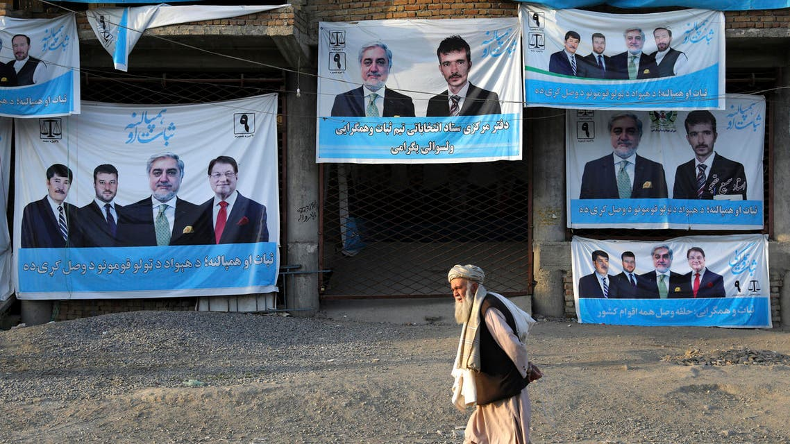 In this Monday, Sept. 23, 2019 photo, an Afghan man walks past election posters for presidential candidate Abdullah Abdullah, on the outskirts of Kabul, Afghanistan. (AP)