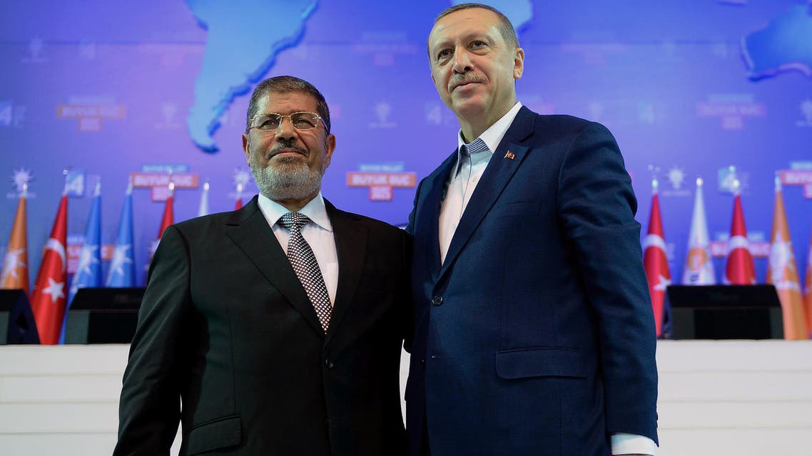 """FILE - In this Sept. 30, 2012 file photo, Turkey's Prime Minister Recep Tayyip Erdogan, right, and Egyptian President Muhammed Morsi attend the congress of Turkey's ruling Justice and Development Party in Ankara, Turkey. Turkey, which had formed an emerging alliance with Egypt's ousted Islamist leader Morsi, on Thursday, July 4, 2013, slammed democratically elected leader's overthrow by the military as """"unacceptable"""" and called for his release from house arrest as Erdogan's Islamic-rooted government has been watching developments in Egypt with concern.(AP Photo/File)"""