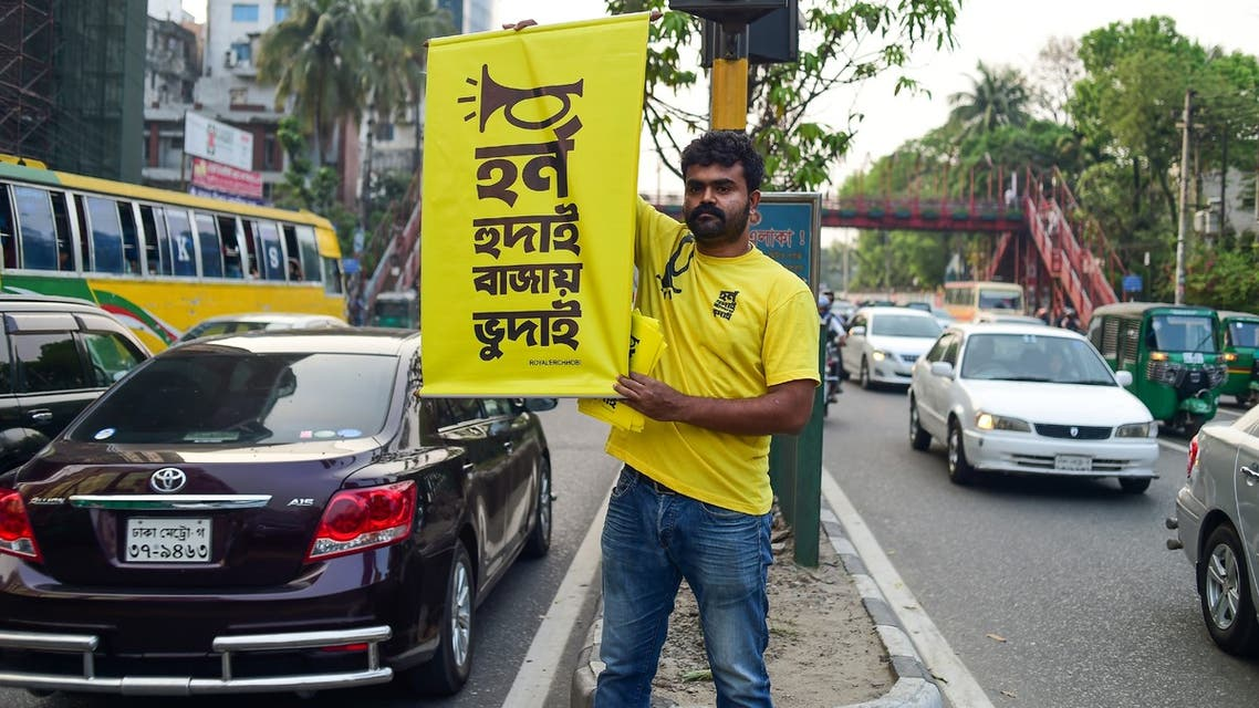 In this photo taken on March 22, 2019, Mominur Rahman Royal holds a banner with a Bengali slogan -- Horn hudai, Bajay Bhudai that translates to only the idiot honks horn unnecessarily -- on a busy street in Dhaka. Bangladeshi Mominur Rahman Royal is stopping traffic -- literally. The 36-year-old is on a one-man crusade to reduce unnecessary honking in one of the world's noisiest cities, where the cacophony of vehicle horns in heavy traffic is as loud as a rock concert.