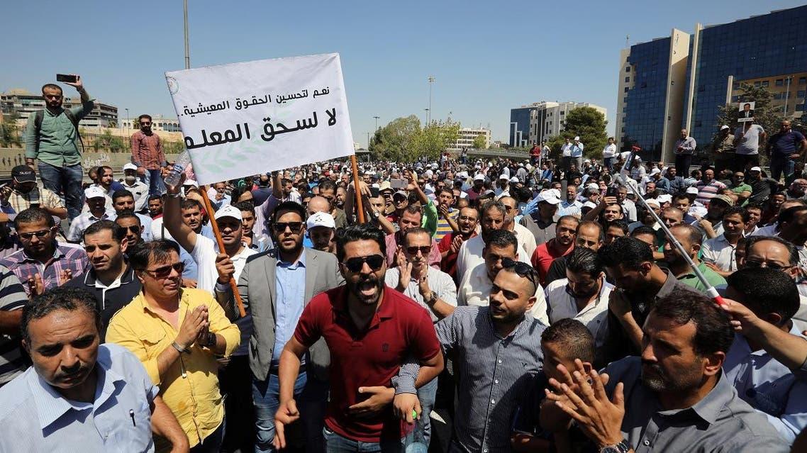 Public school teachers take part in a demonstration near the Prime Ministry demanding a pay raise in Amman. (Reuters)
