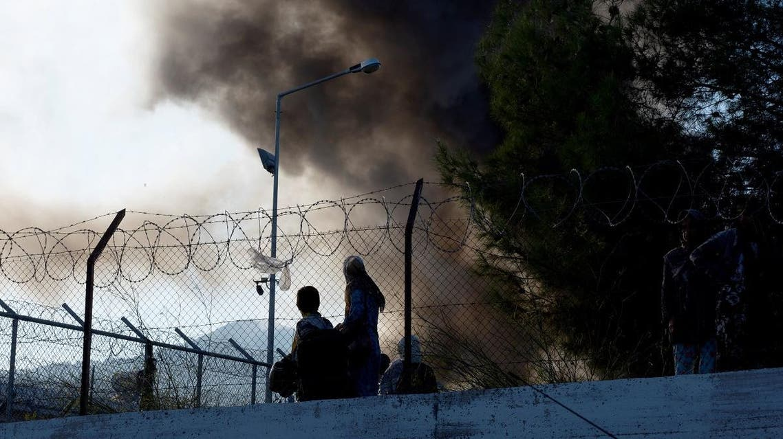 Refugees and migrants try to escape the camp of Moria after a fire broke out in the camp in Mytilene on September 29, 2019. (AFP)
