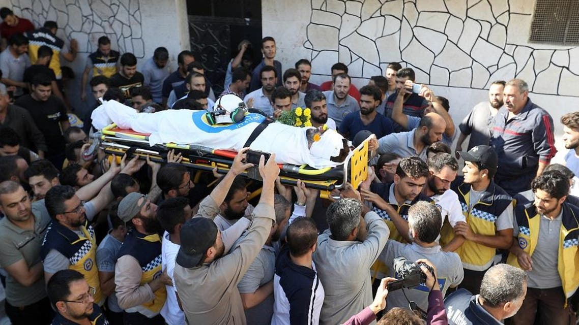 """Members of the Syrian Civil Defence known as """"White Helmets"""" and friends carry the body of citizen journalist Anas al-Dyab during his funeral in Idlib on July 21, 2019. (AFP)"""