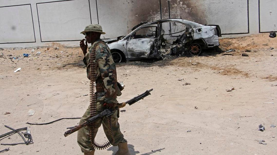 A Somali soldier walks near the wreckage of a car bomb blast near Aden Abdule international airport in Mogadishu, Somalia. (File photo: AP)