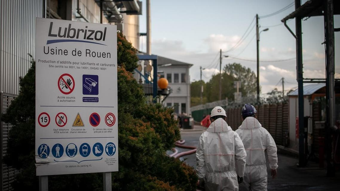Workers walk on September 27, 2019 at Lubrizol chemical factory in Le Petit-Quevilly near Rouen, a day after it was ravaged in a massive fire, spewing smoke and soot that officials insisted posed no health risk. (AFP)