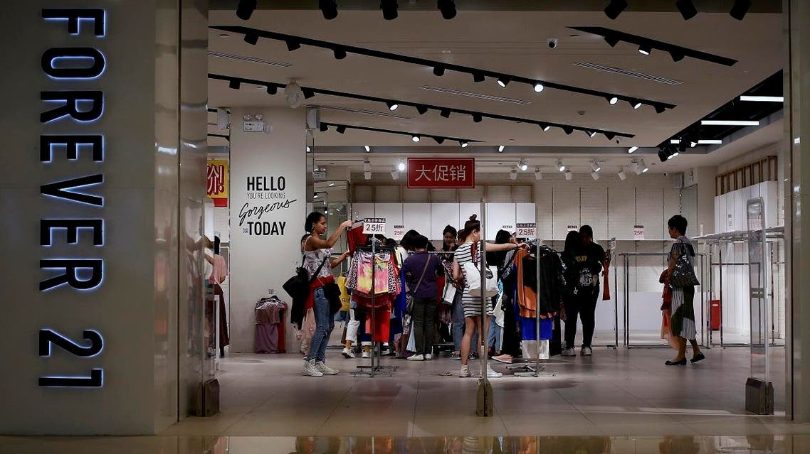 """Women select clothing at an American fast fashion retailer """"Forever 21"""" which is offering clearance discounts at a shopping mall after it pulled out from China's market, in Beijing, Tuesday, May 7, 2019. (AP)"""