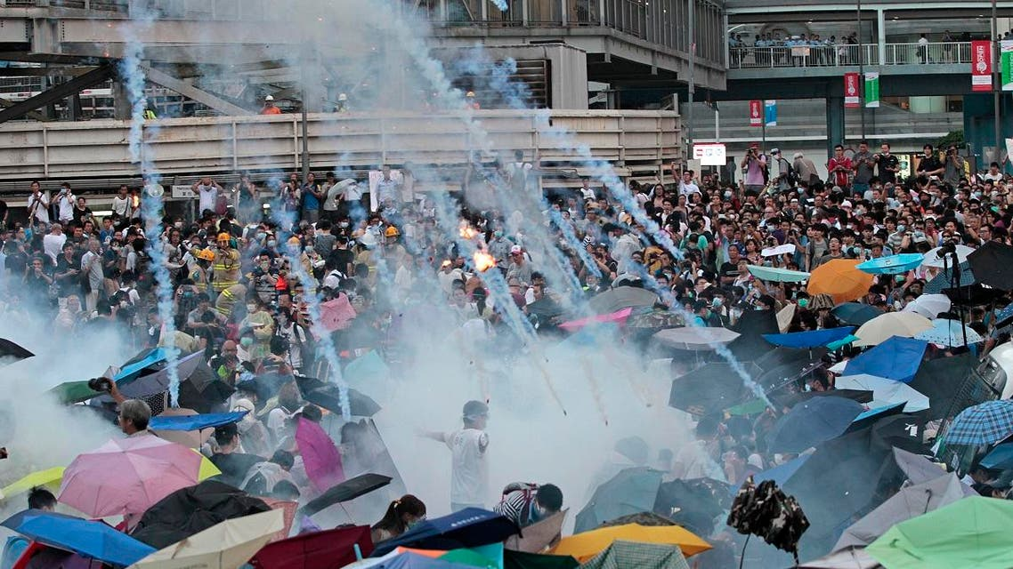 Riot police launch tear gas into the crowd as thousands of protesters surround the government headquarters in Hong Kong Sunday, Sept. 28, 2014.