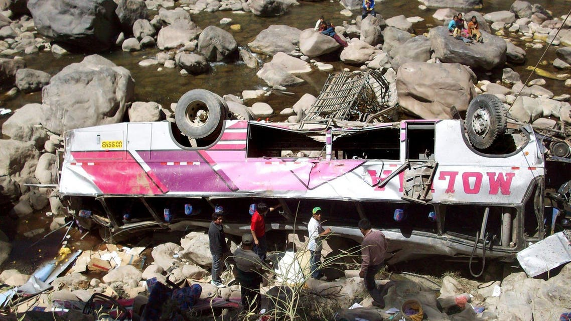 Men stand around a passenger bus that crashed in Huancavelica province, in Peru's southern Andes mountains, Sunday, Aug. 23, 2009. (AP)