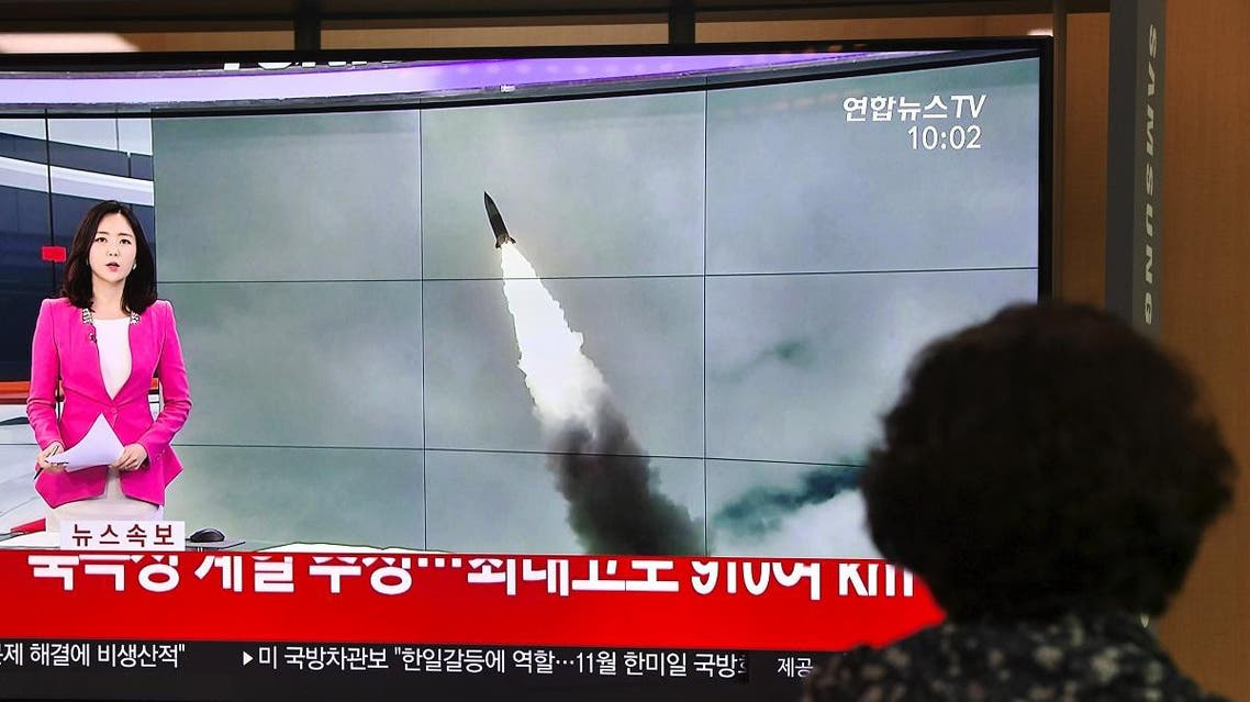 A woman watches a television news screen showing file footage of a North Korean missile launch, at a railway station in Seoul on October 2, 2019. (AFP)