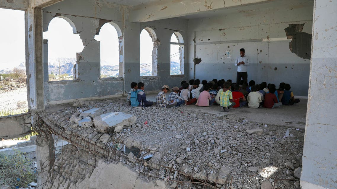 In a tour for the press organised by a damaged school in Yemen's third-city of Taez on September 3, 2019 to attract attention to their suffering, Yemeni children listen to their teacher on the first day of the new academic year in a destroyed classroom at their school's compound which was heavily damaged last year in an air strike during fighting between the Saudi-backed government forces and the Huthi rebels. The classes are given in the undamaged section of the school normally, but the tour was organised to show the press the extent of damage that the school sustained in an attempt to get funding for repairs.