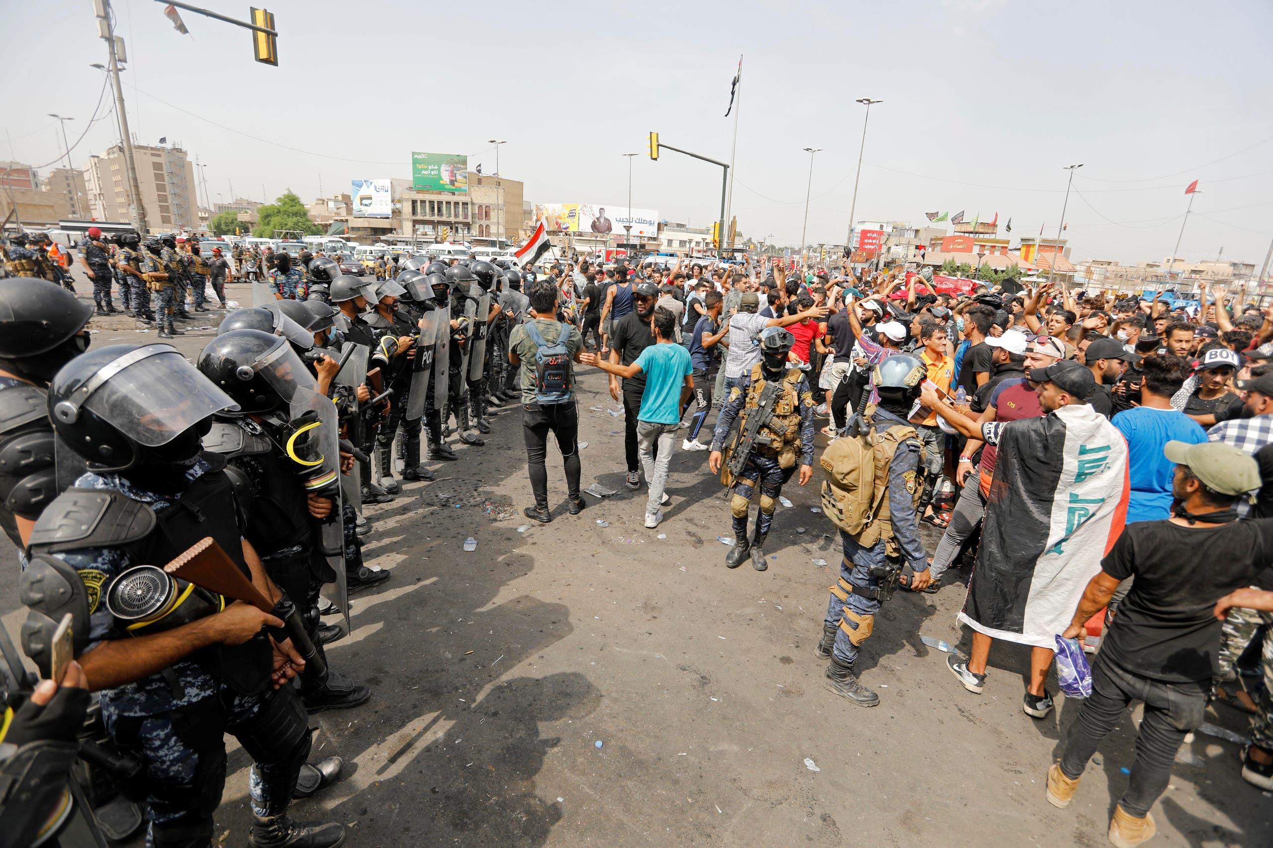 قوات الأمن تقف أمام متظاهرين في بغداد