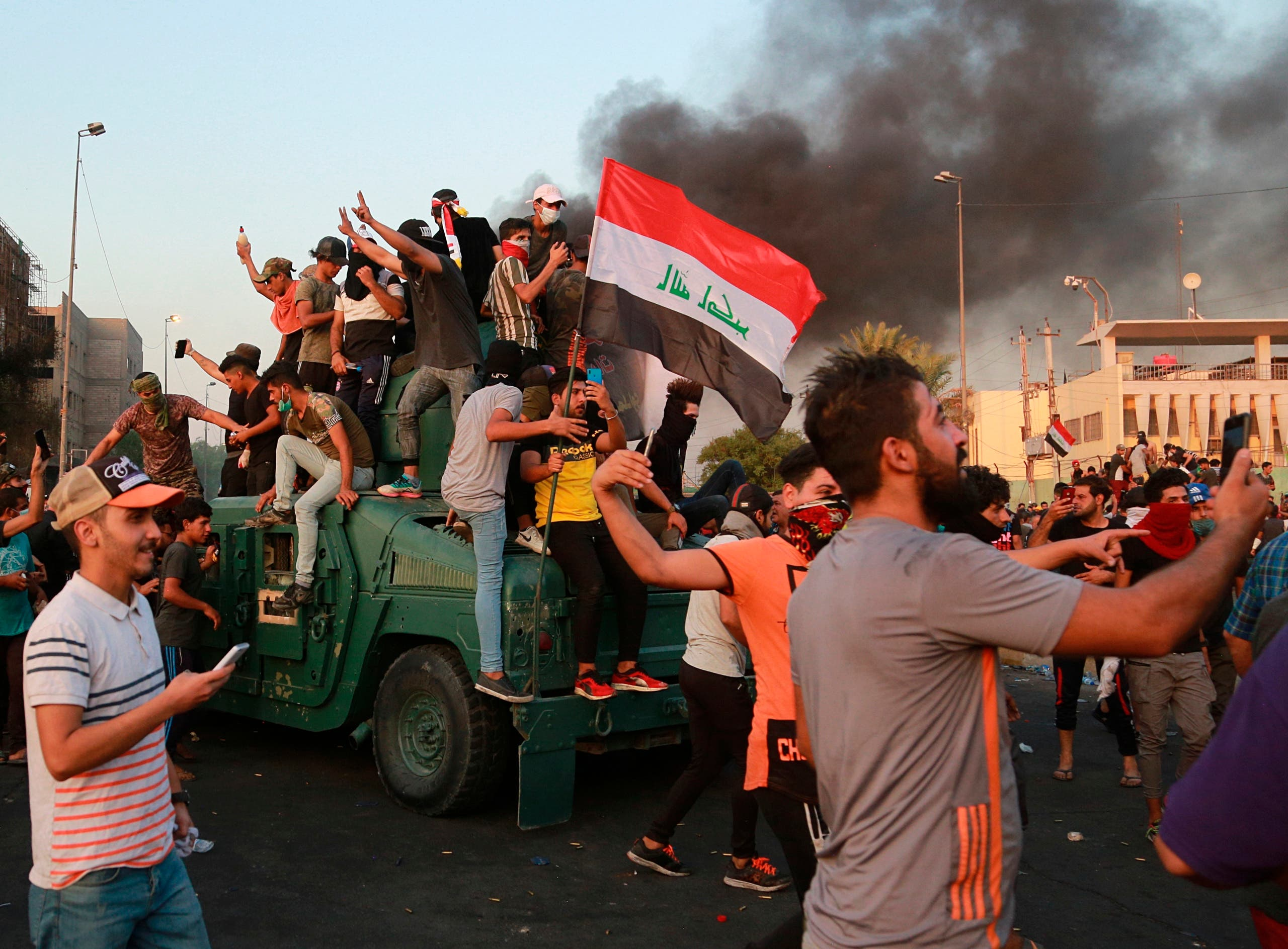 Anti-government protesters take over an armored vehicle before they burn it during a demonstration in Baghdad, Iraq, on Oct. 3, 2019. (AP)