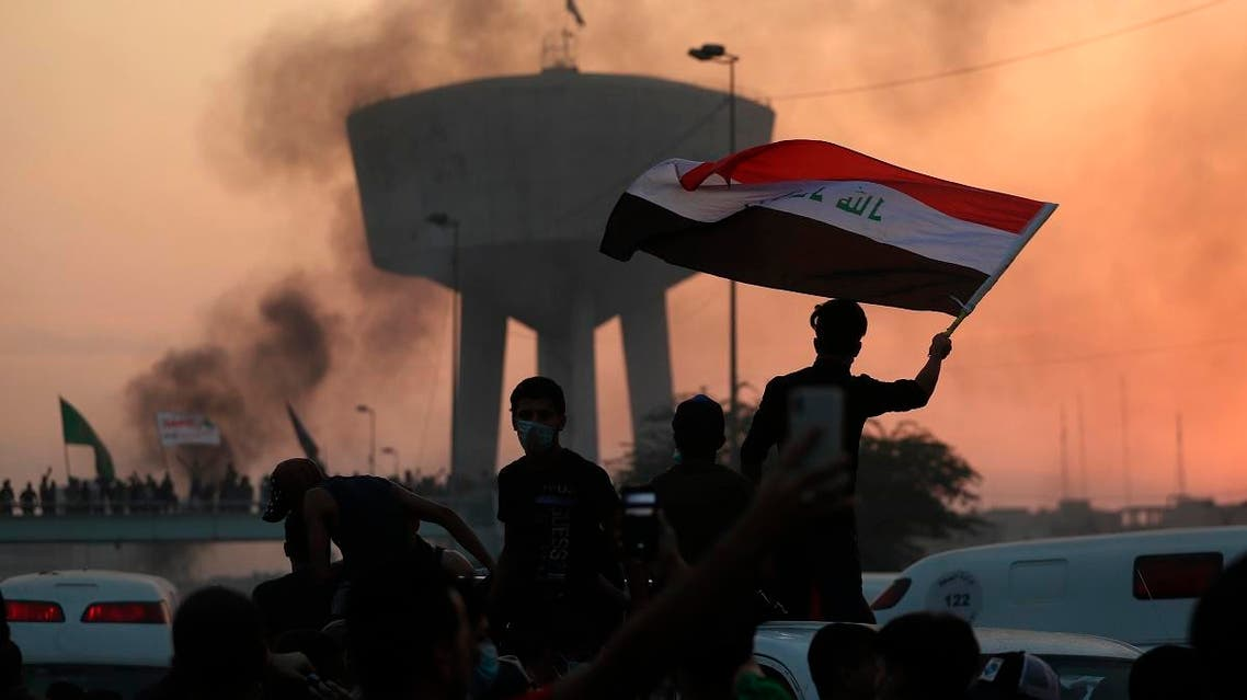 Anti-government protesters wave flags during a demonstration in Baghdad, Iraq. (AP)