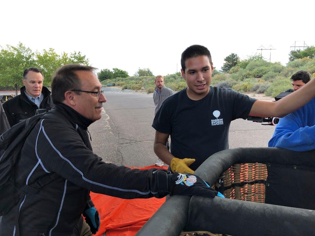 Elijah Sanchez (center), helps passenger board a hot air balloon in Albuquerque on October 1, 2019. (AP)