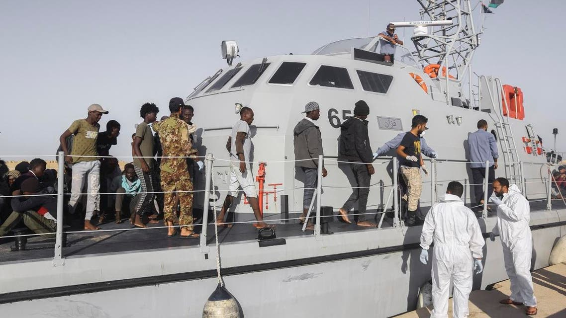 Rescued migrants walk off a coast guard boat in the city of Khoms, around 120 kilometers east of Tripoli, Libya, on October 1, 2019. (AP)