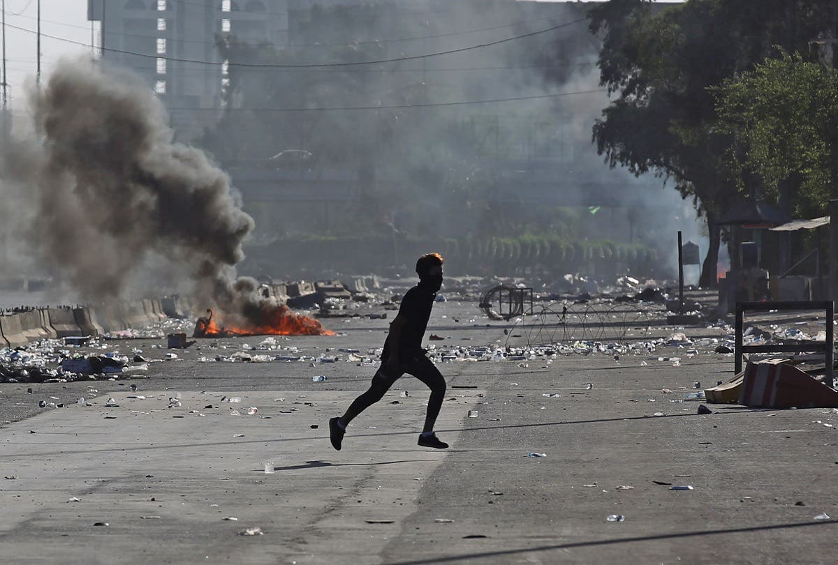 An Iraqi protester runs amidst clashes during a demonstration against state corruption, failing public services, and unemployment in the Iraqi capital Baghdad's central Khellani Square on October 4, 2019. (AFP)