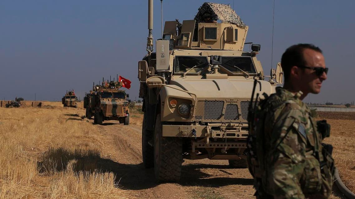"Turkish and American armored vehicles patrol as they conduct joint ground patrol in the so-called ""safe zone"" on the Syrian side of the border with Turkey, near the town of Tal Abyad, northeastern Syria, on October 4, 2019. (AP)"