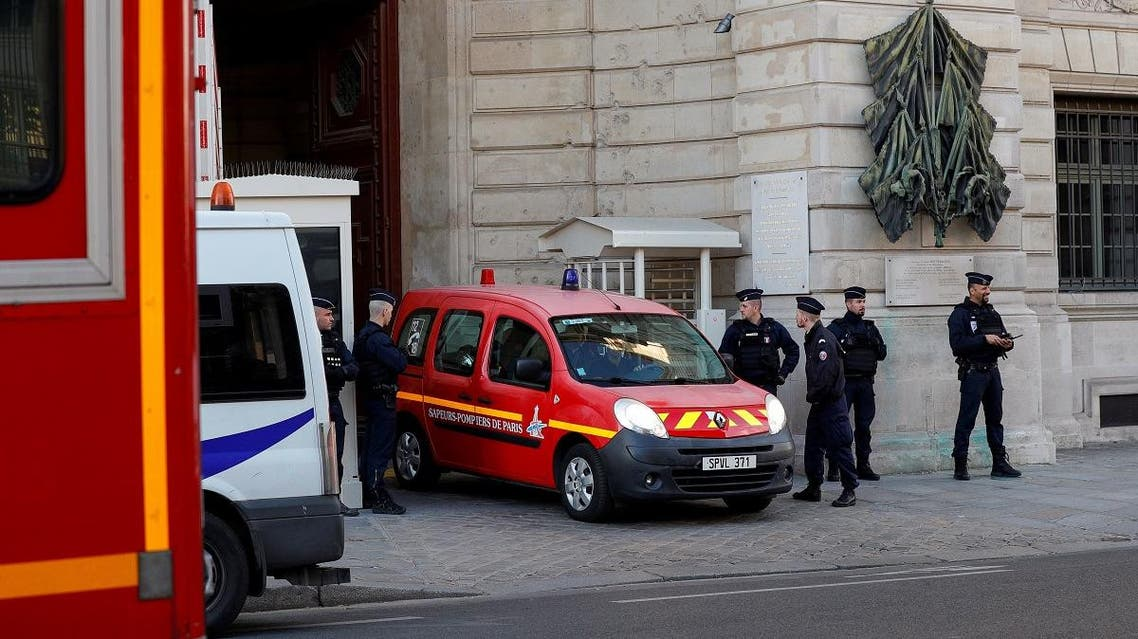 Police officers watch as a firefighter truck exits Paris prefecture de police (police headquarters) on October 3, 2019 after four officers were killed in a knife attack. (AFP)