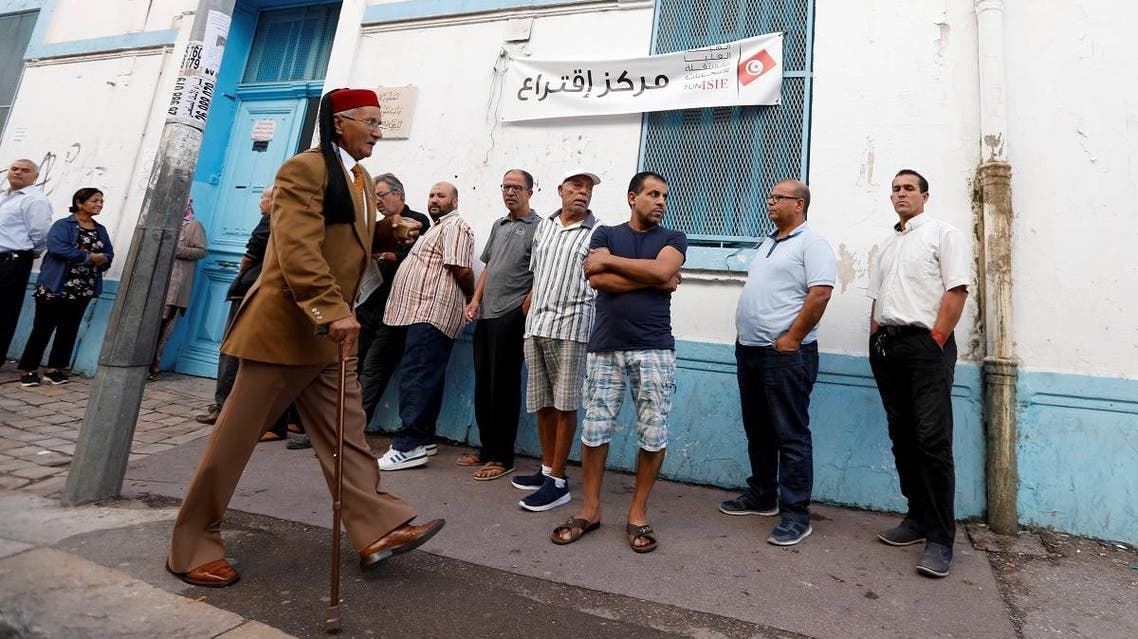 A man arrives at a polling station as people wait to cast their votes during parliamentary elections, in Tunis. (Reuters)