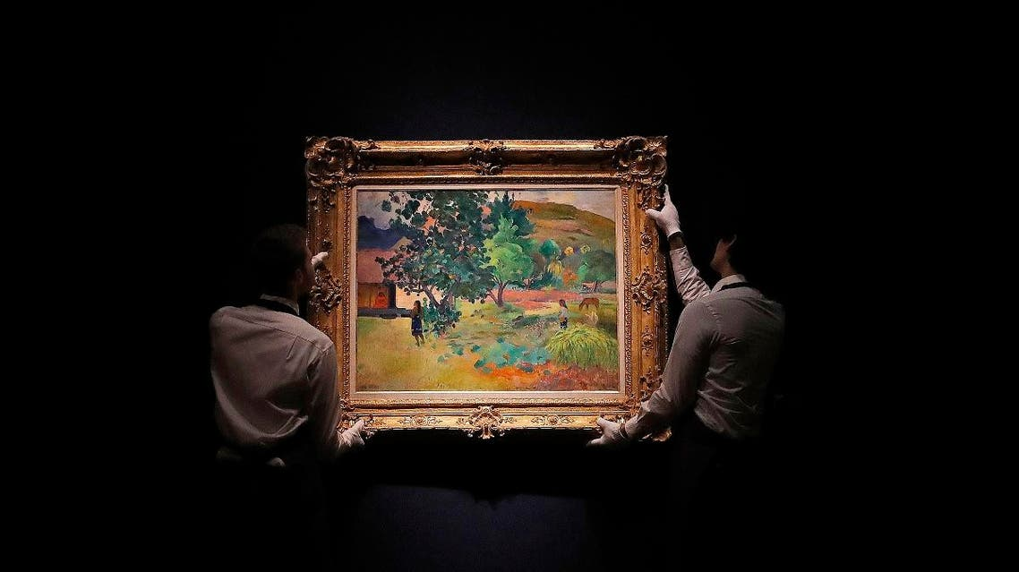 Christie's employees hang up the painting 'Te Fare (La maison)' by Paul Gauguin at Christie's in London. (File photo: AP)