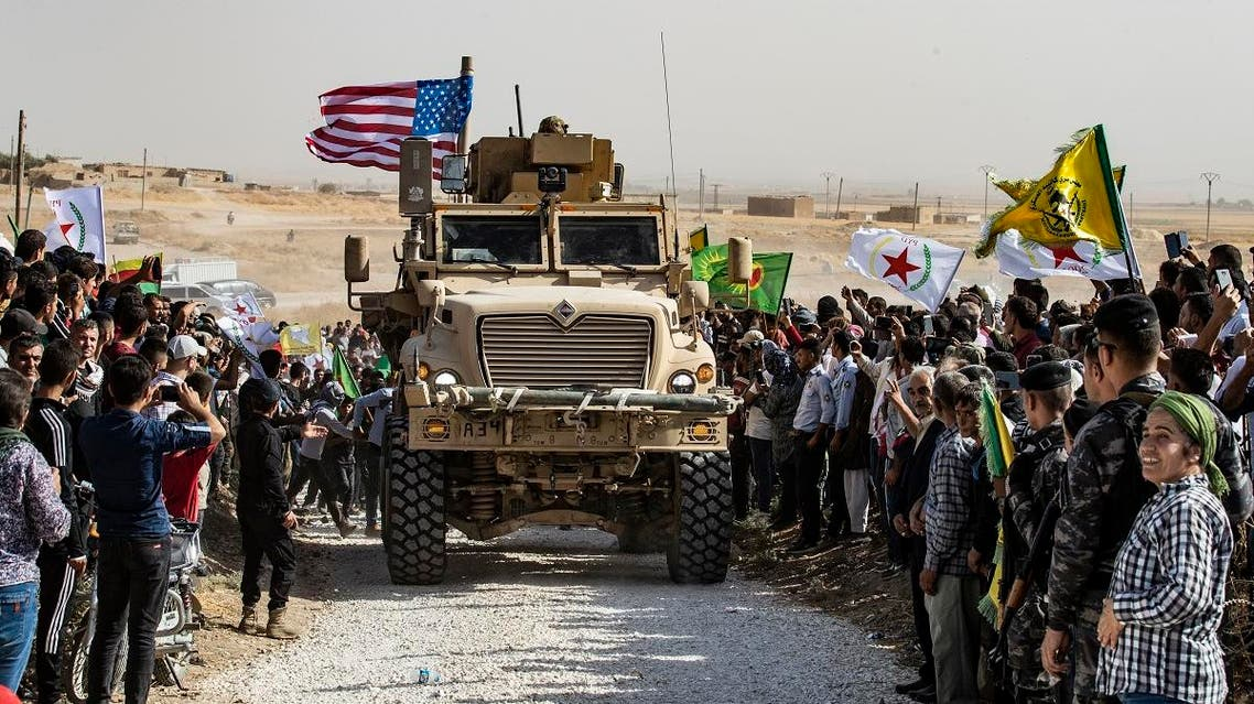 Syrian Kurds gather around a US armoured vehicle during a demonstration against Turkish threats next to a US-led international coalition base on the outskirts of Ras al-Ain town in Syria's Hasakeh province near the Turkish border on October 6, 2019. (AFP)