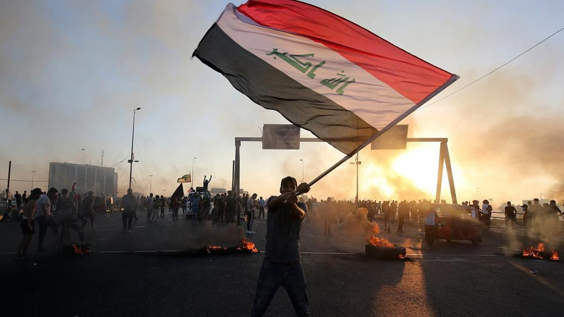 An Iraqi protester waves the national flag during a demonstration against state corruption, failing public services, and unemployment, in the Iraqi capital Baghdad on October 5, 2019. (AFP)
